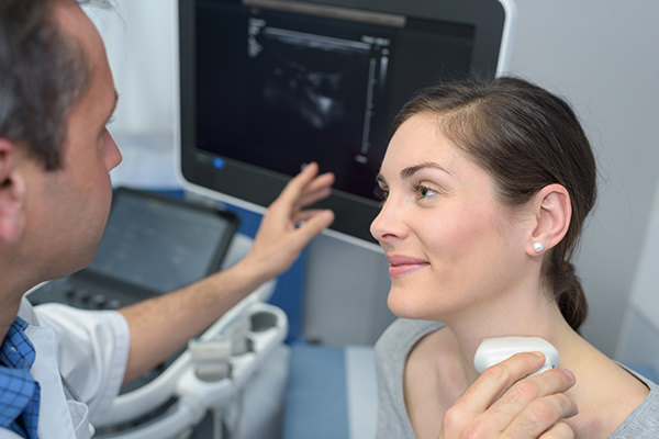 doctor performing neck ultrasound examination on female patient